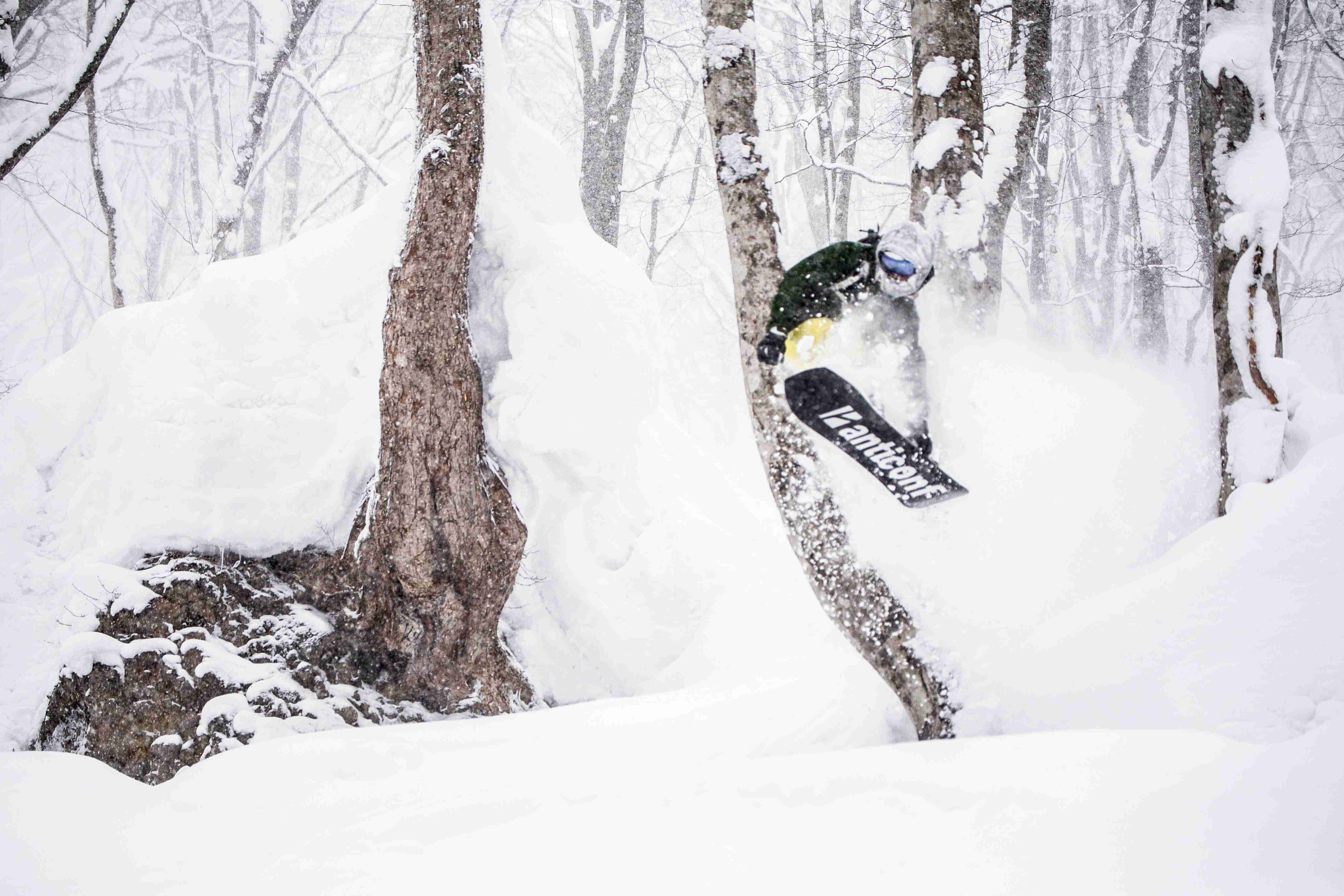 snowboarder in powder jumping in Japan with First Tours