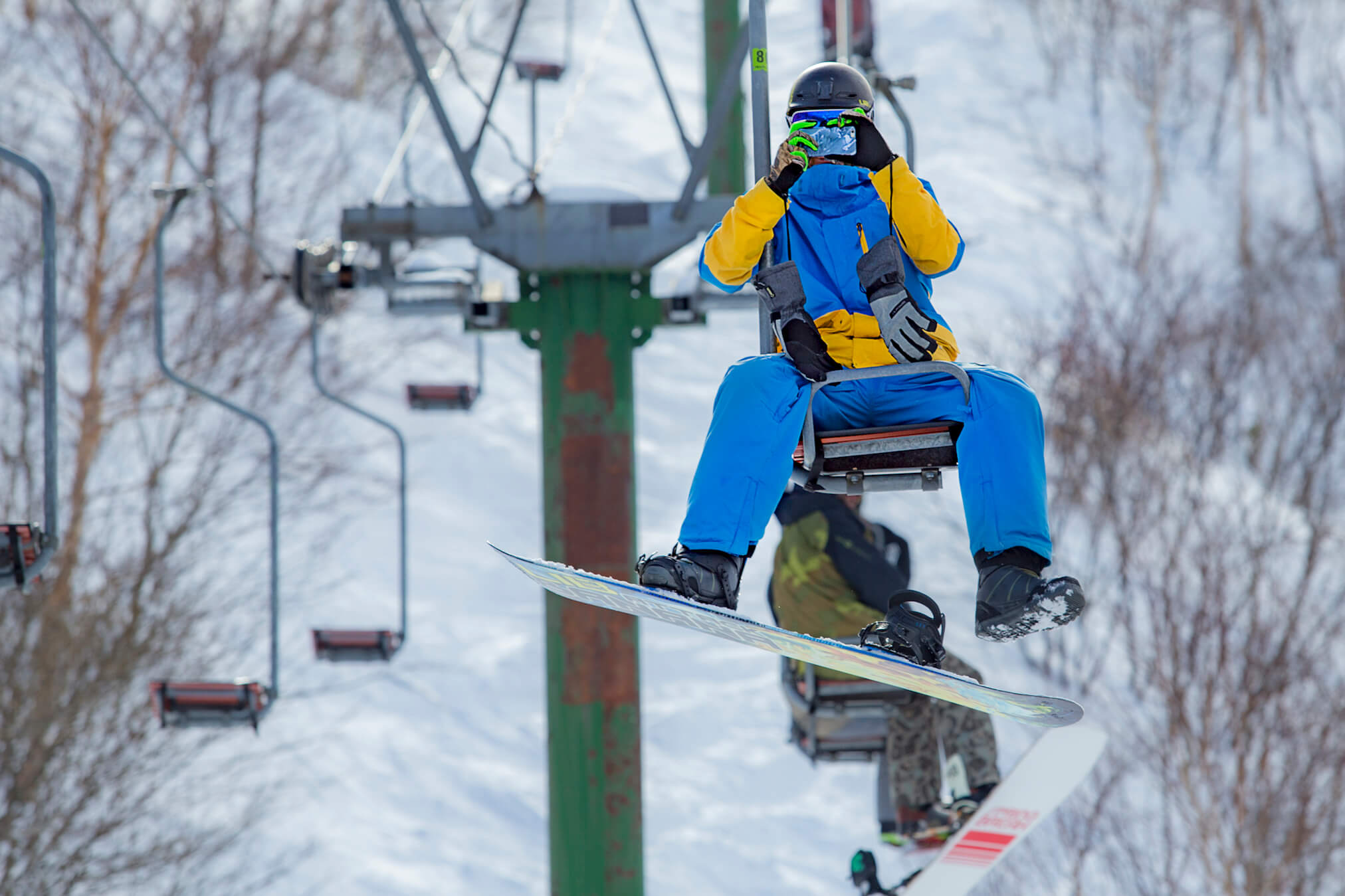 Sitting reverse on pizzabox lift in Madarao during Powder Culture Tour with First Tours