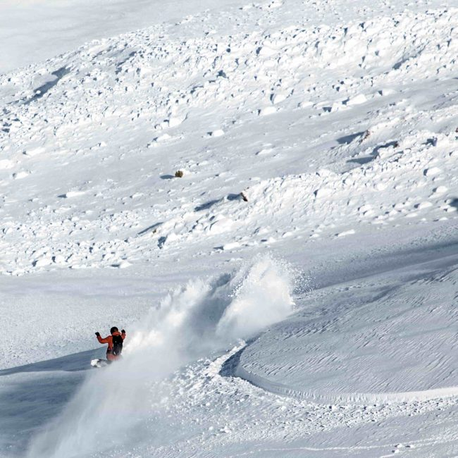 Big spray while snowboarding in Gulmarg with First Tours